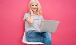 Attractive young woman sitting on the chair with laptop computer